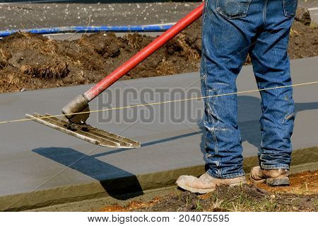 Construction worker uses bull float on the edge of freshly poured concrete on a sidewalk project