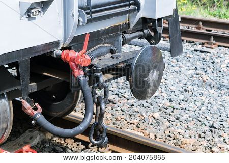Drawbar railway car with an air hose and chain. Rails with concrete sleepers. In the background the rails and gravel. Convex coupling circle. Rail car gray. Day the sun is shining.