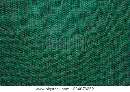 Green, linen cloth close-up background. Fabric khaki teak canvas texture.