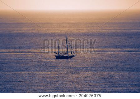 a sailing ship at sea in the evening