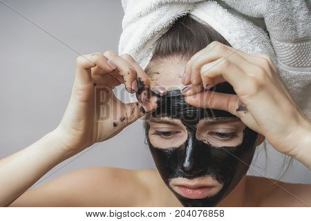 The girl removes the black mask of purification from the face