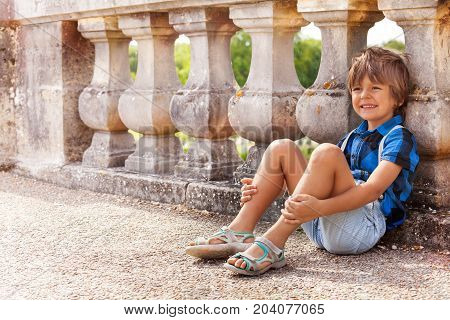Portrait of happy six years old boy sitting on the floor near the stone banister outdoors in summer