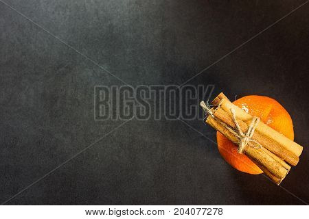 Tangerine Cinnamon Sticks tied with Twine on Black Background Christmas New Year Greeting Card Poster Copy Space Top View Flat Lay