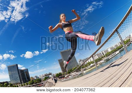 Portrait of female runner jumping while running against cityscape background
