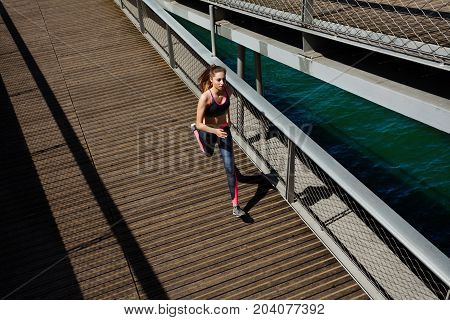Top view portrait of sportswoman running and sprinting across a bridge