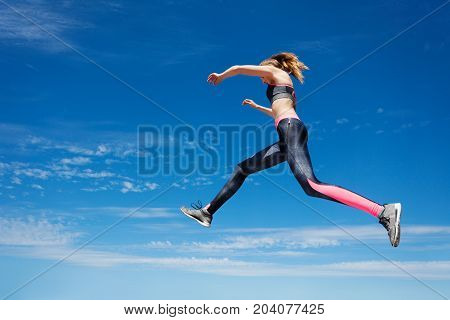 Low angle view portrait of female athlete remaining stationary in air while jumping or running against blue sky background