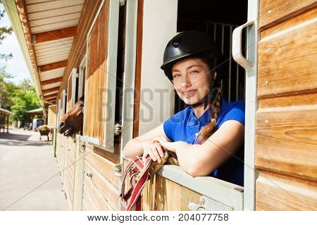 Smiling young woman wearing jockey gear standing inside a box stall at stable, holding reins