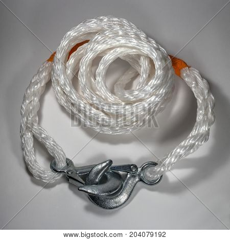 A tow rope with hooks on a light background. White braided synthetic cable.