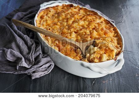 High angel view of a dish of fresh baked macaroni and cheese with table cloth and old wooden spoon over a rustic dark background.