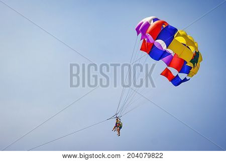 Happy couple Parasailing in Dominicana beach in summer. Couple under parachute hanging mid air. Having fun. Tropical Paradise. Positive human emotions feelings family children travel vacation.