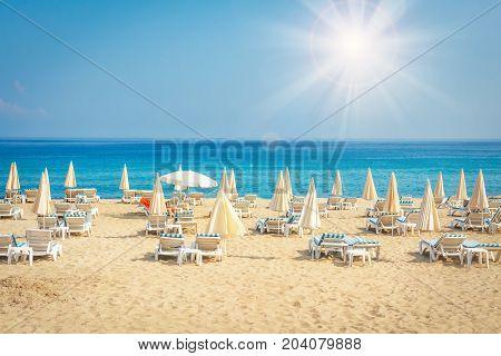 Resort hotel beach on sea. Summer vacation on tropical beach. Sunbeds and umbrellas on sea beach.