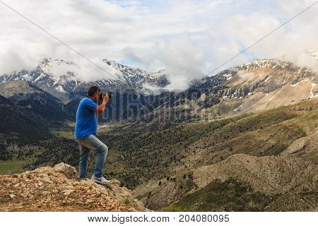 Landscape photographer wearing blue t-shirt and jeans photographing mountain landscape with melting snow on mountain peaks clouds and pine trees