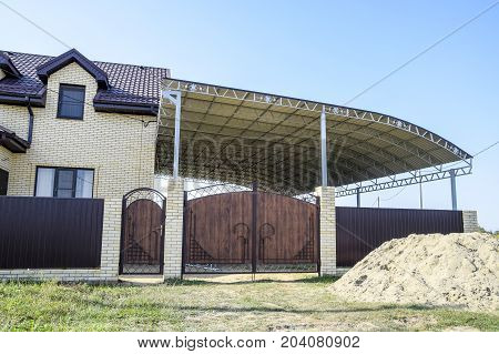 Brick House With A Fence And Gates. A Large Awning With A Steel Frame. View Of A New Built-up Fence