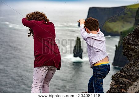 View of Girl and Boy pretending to dive off the Cliffs of Moher Tourist Attraction in Ireland