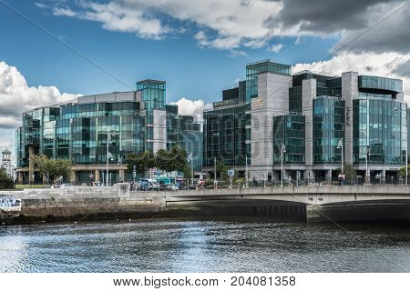 Dublin Ireland - August 7 2017: Modern buildings of IFSC House International Financial Service Center along Liffey River in new financial district. More glass than concrete. Street scene.