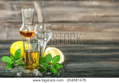 Alcoholic drinks with ice lemon mint leaves on wooden background. Aperitif whiskey gin rum vodka
