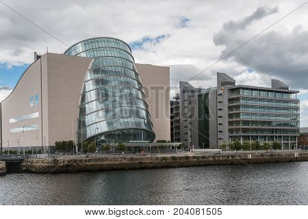 Dublin Ireland - August 7 2017: Barrel shaped convention center buildings along Liffey River in new financial district under heavy cloudscape. Glass and concrete. Street scene.