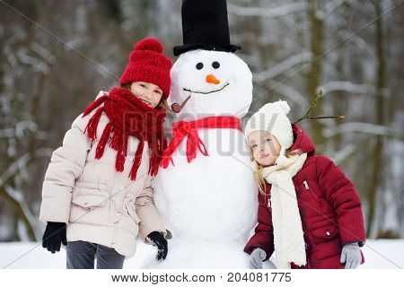 Two Adorable Little Girls Building A Snowman Together In Beautiful Winter Park. Cute Sisters Playing