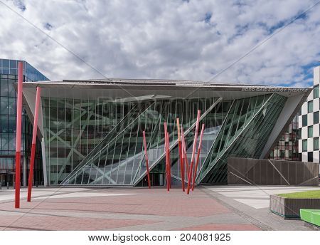 Dublin Ireland - August 7 2017: New modern building of Bord Gais Energy Theater on Grand Canal Square with red sticks art composition in front. Glass Triangles and other shapes. Street scene.