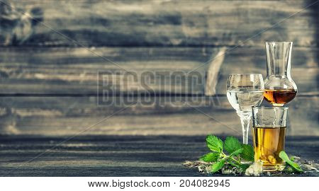 Alcoholic drinks with ice and mint leaves on wooden background. Whiskey gin rum vodka. Vintage style toned picture