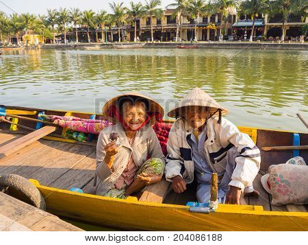 HOIAN, VIETNAM, SEPTEMBER, 04 2017: Unidentified old couple in the traditional boats in front of ancient architecture in Hoi An, Vietnam. Hoi An is the World's Cultural heritage site, famous for mixed cultures architecture.