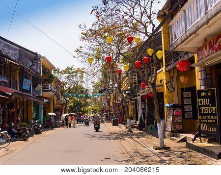 HOIAN, VIETNAM, SEPTEMBER, 04 2017: Unidentified people walking in the street view with old houses, and colorful lanters made of paper, in Hoi An ancient town, UNESCO world heritage.