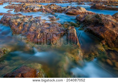 Silk effect on the water in the river Tinto with stones of color bronze, near the village of Niebla, in Huelva