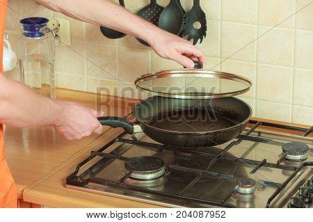 Closeup of human hand with heating frying fry pan on burning gas burner stove.