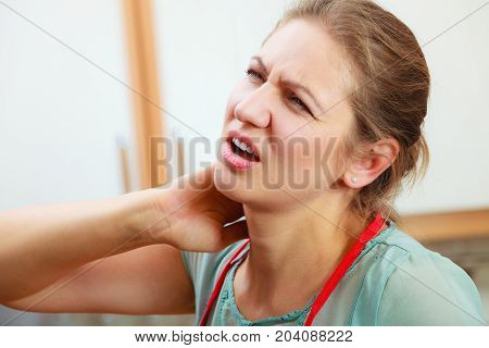 Overworked mature woman suffering from neck pain. Stressed female in kitchen.
