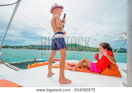 Cute kids on a boat trip. Boy is playing a toy guitar for his beautiful girlfriend