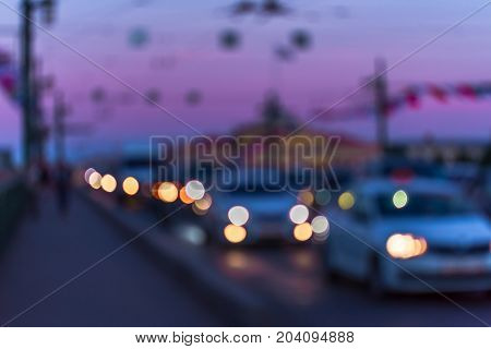 Abstract defocused image of cars driving in city twilight