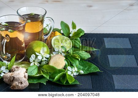 Two transparent cups with tea. Green, black, herbal, jasmine tea with lemon and ginger. Theme of tea. Cooking, tea packing, food production, restaurant business