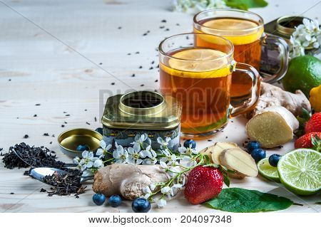 Tea background , space for text, light. Tea in transparent mugs with lemon, ginger, lemons, limes, mint, cherry blossoms. Stylish, colorful background. Food industry, tea packing, restaurant business
