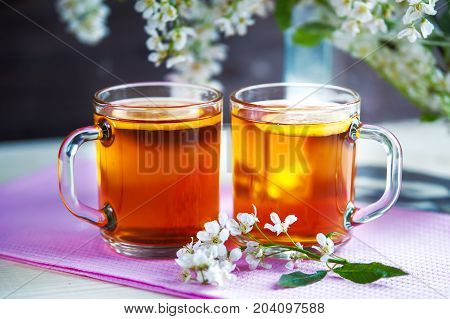 Two cups of black tea with lemon,  cherry flowers. Still life. Food industry, tea packing, restaurant business
