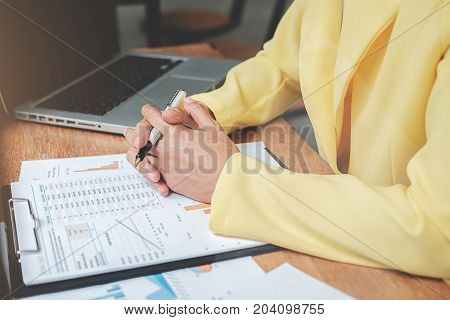 Businesswoman Working At His Coffee Shop And Using Laptop,  Discussing The Charts And Graphs Showing
