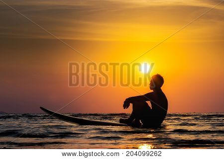 Silhouette of surf man sit on a surfboard. Surfing at sunset beach. Outdoor water sport adventure lifestyle.Summer activity. Handsome Asia male model in his 20s.