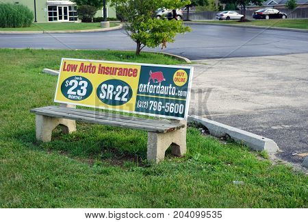 CREST HILL, ILLINOIS / UNITED STATES - JULY 20, 2017: An advertisement on a bench, at a bus stop on Plainfield Road, advertises low auto insurance.