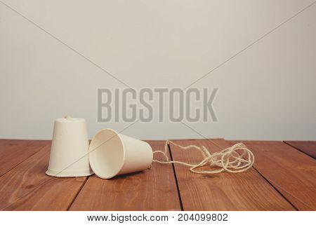 Vintage tone of classic paper cup phone on wood background
