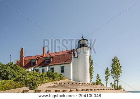 Point Betsie Lighthouse with its red roof and white building. The moon is rising just behind the building.
