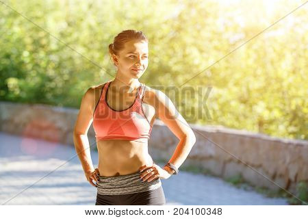Young slim girl resting after run training in the park. Smiling runner woman standing outdoors
