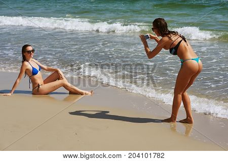 Two young women having fun at the seaside she takes his girlfriend on a mobile phone