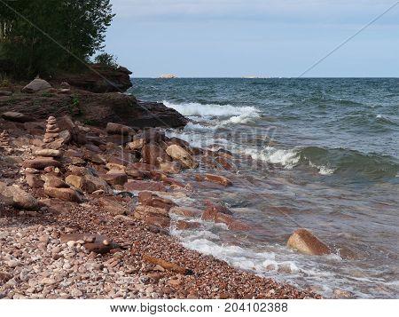 Waves of Lake Superior surge toward the rocky shore of Presque Isle Park in Marquette Michigan.