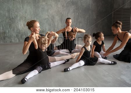 Young women ballerinas in black dresses white pantyhose and pointe help stretch out before the dance and sits on a string of small inattentive little girls in a black dress to dance ballet well