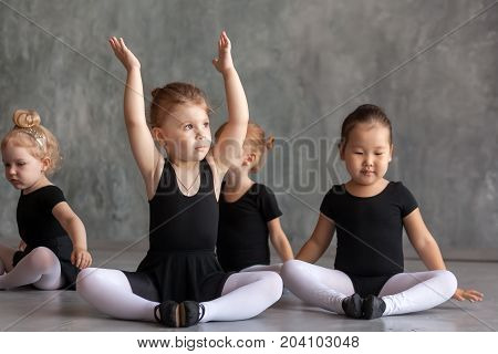 small girls of the ballerina European and Asian nationalities black dresses and tights puffy make a warm-up before the ballet in a dark dance studio