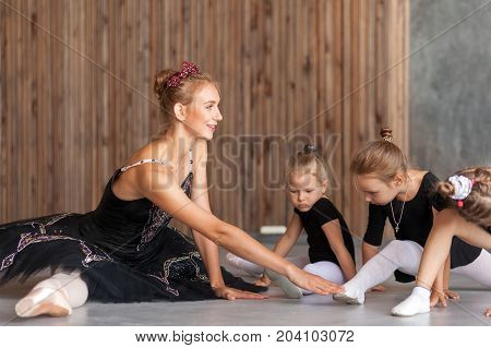 young woman ballerina in a black dress white pantyhose and pointe shoes help stretch before the dance of small inattentive girls in a black dress to dance ballet well in a dark dance studio