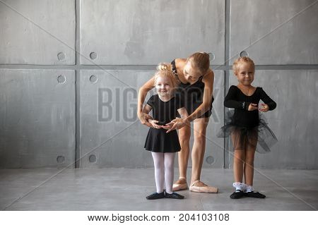a young woman ballerina in a black dress white pantyhose and pointe shoes teaches to dance the ballet of young girls ballerinas in black dresses and tights in a dark dance studio