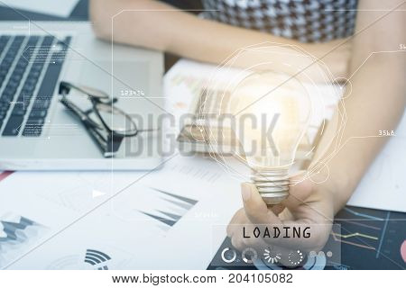 Business hand holding light bulb on document desk concept of new technology ideas with innovation and creativity.