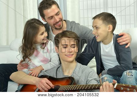 Family listening how boy playing on guitar while sitting on couch