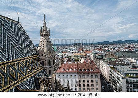 Vienna, Austria - August 16, 2017: Panoramic view of Vienna from the roof of Cathedral of St Stephen. Built in romanesque and gothic style, with its multi-coloured tile roof is a city's symbols