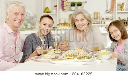 Brother and sister having breakfast together with their grandparents